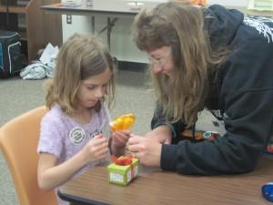 4-H volunteer leader Bridie helps Rowynn with her scrapbooking project