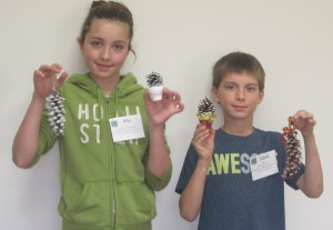Alley and Caleb show off the projects they made in Holiday Pinecones and Acorns Session.