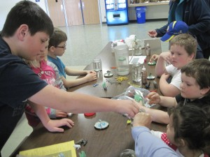 Austin, 4-H youth leader, helps youth create snow globes.
