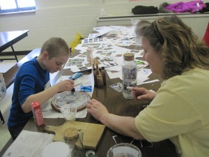 Ben receives assistance from Beth in the Decoupage session