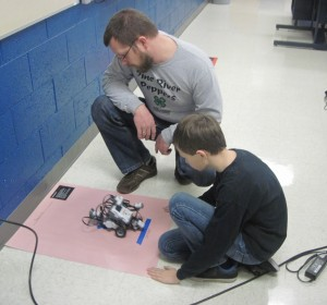 Hunter shows Peter his robot completing a challenge during the Robotics Session