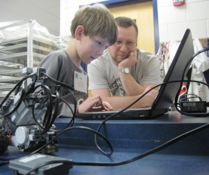 Ian shows his father how to program the robot he built to complete challenges.