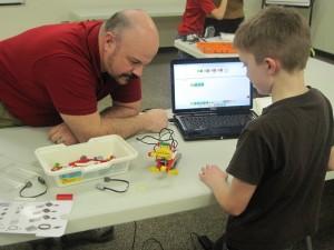 Jayden assembles his We Do robot as Pat looks on